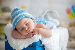 有被编织的帽子的小男婴,睡觉与逗人喜爱的玩具熊 免版税库存图片