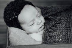 有被编织的帽子的新出生的睡觉的男婴 免版税图库摄影