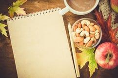 有被编织的毯子、一个杯子热的可可粉和快餐的空白的棕色笔记本 感恩天概念 免版税库存照片