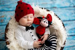 有被编织的瓢虫帽子和裤子的小男婴在篮子 图库摄影