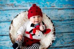 有被编织的瓢虫帽子和裤子的小男婴在篮子 库存照片