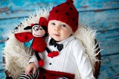 有被编织的瓢虫帽子和裤子的小男婴在篮子 免版税图库摄影