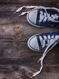 有被解开的白色鞋带的老被佩带的蓝色运动鞋 免版税库存图片