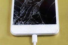 有被连接的缆绳的残破的智能手机 保存在修理或处置前的数据  免版税库存照片