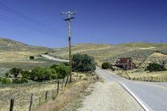 有被铺的路的生锈的老红色谷仓 免版税库存照片
