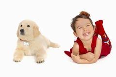有被隔绝的一只金毛猎犬小狗的小女孩 免版税图库摄影