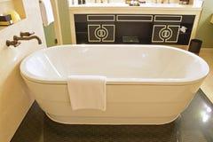 有被隔绝的浴缸,大理石墙壁和versace的经典设计卫生间启发了橱门 免版税库存图片