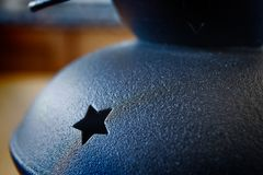 有被雕刻的星的黑金属灯台在一张木桌上 免版税库存照片