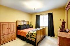 有被雕刻的木床的明亮的黄色卧室 免版税库存照片