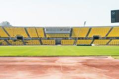 有被风化的塑料位子的空的老体育场 库存照片