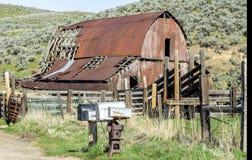 有被风化的邮箱的老农厂谷仓 库存图片