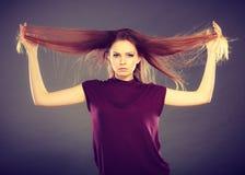 有被风吹头发的可爱的深色的妇女 免版税库存照片
