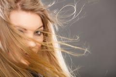 有被风吹头发的可爱的白肤金发的妇女 库存照片