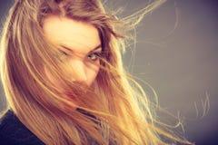 有被风吹头发的可爱的白肤金发的妇女 免版税库存照片