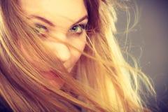 有被风吹头发的可爱的白肤金发的妇女 图库摄影