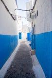 有被绘的蓝色墙壁的狭窄的老街道 免版税图库摄影