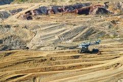 有被暴露的色的矿物的墙壁地表矿山,在底部的坑采矿设备 免版税库存照片