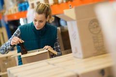 有装瓶的年轻微笑的女性啤酒厂工作者 免版税库存图片