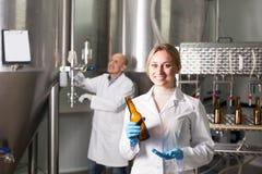 有装瓶的机械的微笑的女性啤酒厂工作者 免版税库存图片