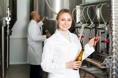 有装瓶的机械的微笑的女性啤酒厂工作者 库存图片