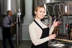 有装瓶的机械的微笑的女性啤酒厂工作者 库存照片