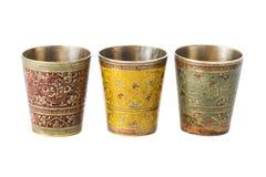 有装饰品的三个古铜色杯子在白色背景 库存照片