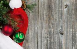 有装饰品的圣诞老人盖帽和在木板的常青分支 库存照片