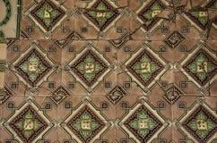 有装饰品的老和损坏的方形的瓦片 库存照片