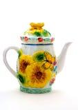 有装饰品花和蝴蝶的黄色瓷茶壶 免版税库存照片