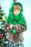 有装饰玩具球的愉快的女孩由圣诞树 图库摄影