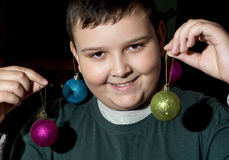 有装饰球的滑稽的圣诞节男孩 免版税库存照片