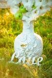 有装饰的白色葡萄酒花瓶在自然背景 免版税库存图片