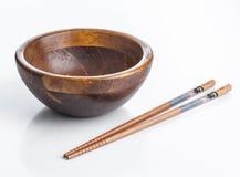 有装饰的筷子的空的木碗 免版税库存照片