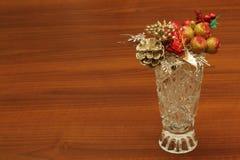 有装饰苹果,在自然木背景的锥体原始的样式和花束的美丽的老水晶花瓶  免版税库存图片