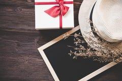 有装饰装饰的礼物盒,花和帽子在黑板上 老木背景,拷贝空间 免版税图库摄影