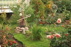 有装饰风车的花卉草坪 免版税库存照片