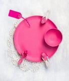 有装饰鸟的桃红色在鞋带小垫布和灰色桌的板材和标志 库存照片
