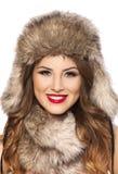 有裘皮帽的美丽的微笑的少妇 免版税库存照片