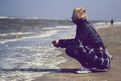 有裙子的白肤金发的妇女在海洋前面 免版税图库摄影