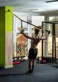 有裸体躯干的人和在健身房的肌肉后面喜欢训练, trx 有躯干的人,运动员,运动员,肌肉强壮男子 免版税库存照片