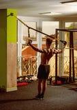 有裸体躯干的人和在健身房的肌肉后面喜欢训练, trx 有躯干的人,运动员,运动员,肌肉强壮男子 库存照片