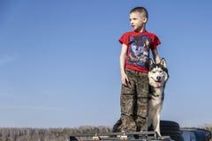 有西伯利亚爱斯基摩人狗的男孩在蓝色背景 家庭生活方式 在城市之外的步行 免版税库存图片