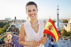 有西班牙旗子的妇女游人在公园Guell,巴塞罗那,西班牙 图库摄影