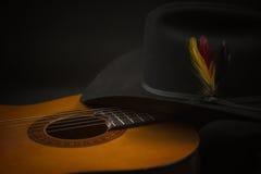 有西部帽子的老吉他 免版税库存照片