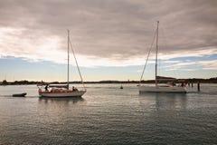 有见面在澳大利亚湖的furled风帆的两条风船 免版税图库摄影