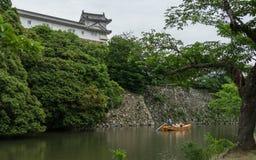有观光的游人和指南的传统小船在姬路城内在护城河  姬路,兵库,日本,亚洲 免版税库存图片