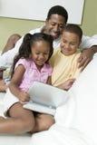 有观看在便携式的DVD机的孩子的父亲电影 免版税库存图片