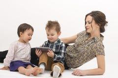 有观看在手机的两个孩子的年轻母亲动画片 免版税图库摄影