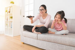 有观看滑稽的电视频道的女孩的妈妈 免版税库存照片