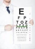 有视力检查表的男性眼科医生 图库摄影